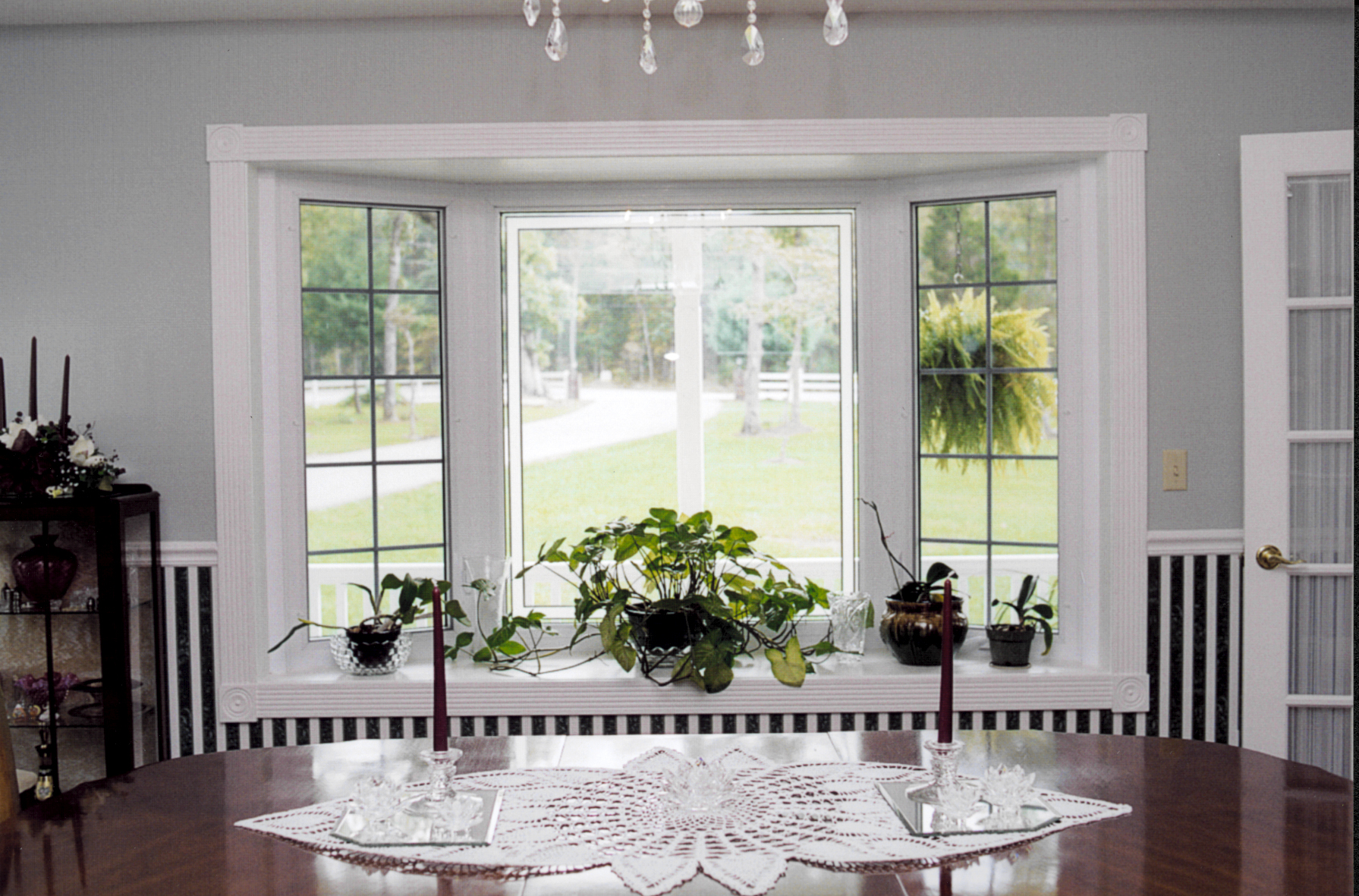 Bay Windows With Vivid Ornamental Plants And Beautiful Vases Large Dining Table Luxurious Crystal Pendant Lamp
