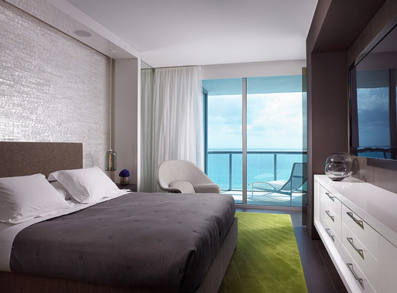 beautiful bedroom concept with ocean view also elegant white drawers with large wall mount tv completed with cozy seating with fresh green rug