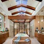 beautiful design of bathroom with giant cream bathtub also astonishing wooden sloping ceiling with large glass sliding door and glossy wooden cabinet in laminate flooring
