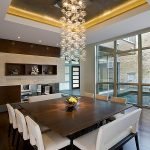 beautiful dining room design with large square wooden table also elegant black and white leather chairs with large glass window and astonishing cyrstal lamp with walll mount shelve in laminate flooring