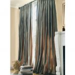 beautiful long grey pleat curtain a pile of books statue ornament
