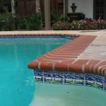 beautiful orange swimming pool borded with white lines white swimming pool bottom dark wood patio doors blue and colorful tile for pool edge mini gold fountain wood fence pave flooring