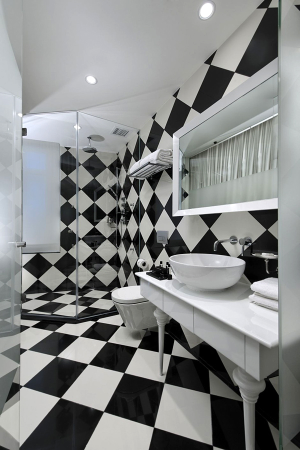 black and white ceramic tiled wall and floor white simple counter white round vessel sink white