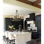 black and white kitche l-shaped with magnificent white cahirs and classic chandelier with ravishing potted flower in granite tile flooring