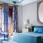 blue bed with large colorful wall painting and eatiful motive curtain with eegant chairs in laminate flooring