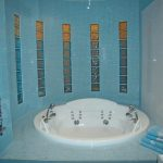 blue tiled bathroom wall round white jacuzzi iron towel hanger blue towels white towels glass small square lined window pale blue tiled flooring white wall
