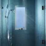 blue tiled shower wall glass shower door with iron knob white framed window white ceramic flooring iron showers glass shower wall