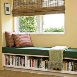 bookshelves with bench under the window  window  blinds strip-patterns decorative pillows  book arrangements