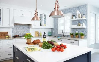 brass cute hanging lamps black island with white counter white ceiling downlight white cabinets white framed window grey counter blue tiled backsplash white upper cabinets