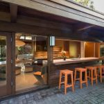 brick patio flooring wood orange stools wood exterior wall glass patio door with wood frame brown counter metal undermount sink wood framed folded window white sconce oval wood dining table
