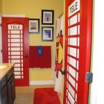 brown tiled flooring red mat unique red telephone booth themed door yellow wall white ceiling black cabinet with brown counter and white sink red towels cartoon themed shower curtain