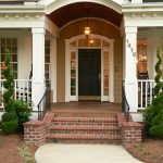 brownish green wooden exterior wall white painted window frame white painted columns and fence bricked stairs stoned walkways simple beautiful pendant lamp beautiful front entry black painted front door