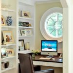 brwon leather chair white open shelving white ox eye window white floating desk with dark brown counter pale yellow wall white ceiling small glass vase downlight brown tiled flooring