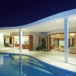 contemporary house pool free shaped pool white poles white wall wood framed glass sliding doors downlights cream sofas colorful striped deck chair wood dining table wood dining chairs