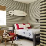 cream carpet flooring cream blac striped wallpaper white ceiling wood chair red side table black bed frame brown window shade black sconce white surfing board red and white pillowd pale blue bed cover