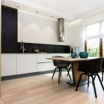 cute black and white kitchen and dining area with simple white cabinet also interesting large glass window overlooking the outside view completed with flat ceiling design in laminate flooring idea