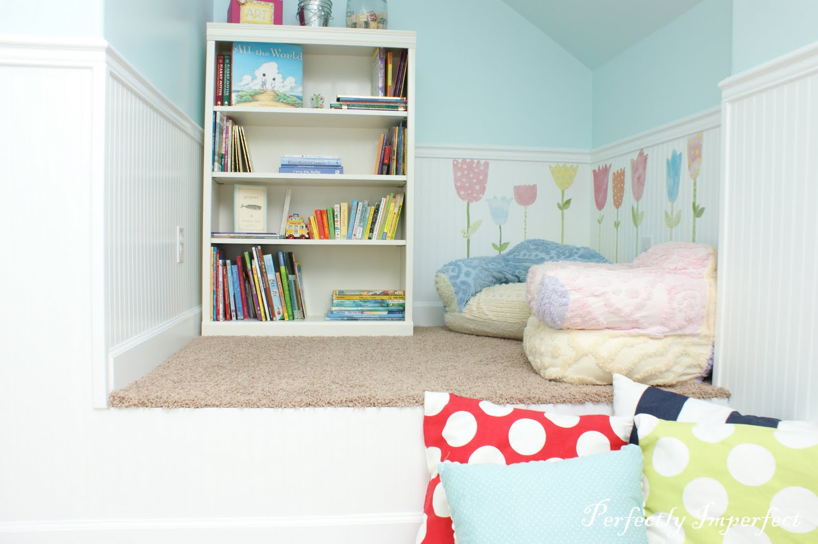 cute reading area with cozy reading nook and elegant small bookshelve with calming blue wall and polcadot cushion for small house idea