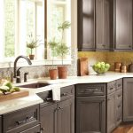 dark wood cabinet with white marble countertop hardwood flooring beige wall white framed windows black hanging lamo dark wood upper cabinets yellow tiled backsplash clay pots brown undermount sink