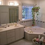 doorless bathroom with large bathtub and sprayer system in gold-accent hanging pot and its plant ornament twin bathroom sinks with under white cabinet systems and lage frameless mirror