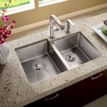double sink for kitche with double stainless steel faucet artistic white porcelain vase with beautiful flowers arrangement light gray granite-surface countertop