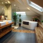 elegant bathroom ceoncept with ravishing sloping ceiling and mesmerizing wooden seating with large white bathtub