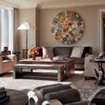 enchanting living room design with elegant soft brown accent feat creative round wall decoration also with ravishing wooden table in large carpeting