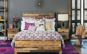ethnic bedroom design with ravisihing old style bed with purple accent also wooden small cabinet in purple rug