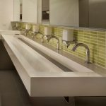 extra large trough sink with multiple taps and green tiles backsplash