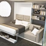 folding bed in minimalist style with single shelf under the bed comfy grey sofa with black-white pillows grey tone book shelving system