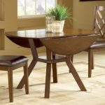 glossy soft wood finish double drop leaf dining table  a pair of dining chairs with leather seating