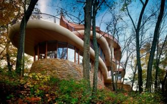 gorgeous curvy architecture blended with nature house brick stone wall foundation floor to ceiling windows with wood frames extended wood ceiling wood balcony railing