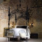 gothic canopy bed white bedding set black pillow black with gold floral print pillow elegant gold framed mirror with white chandelabra white chair raw stone wall black unique canopy frame