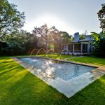 great backyard green grass outdoor ground cream wall white wall white framed window rectangular pool stone tiled pool border amazing pool fountains wood framed window white chimney