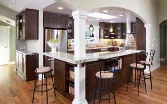 great l-shaped kitchen with glossy marble countertop with interesting wooden cabinet and interesting barstool with multiple downlight in laminate flooring