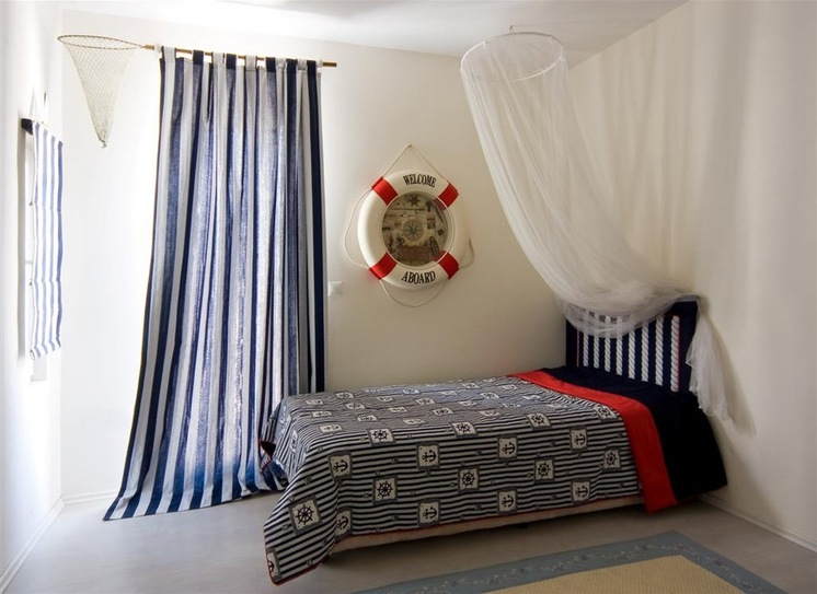 grey cement flooring cream with blue edge rug white wall white ceiling white and navy blue vertical striped curtain white mosquito net dark blue bedding set