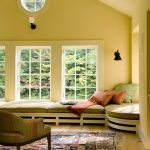 hardwood flooring colorful patterned rug yellow wall white framed windows black sconce white ox eye window green yellow pink stripped easy chair green day bed green and pink pillows