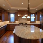 high class look granite countertop with clear natural lines triple pendant lamps with black metal hanger and chain  wood-finish wood for kitchen floor hardwood cabinetry system