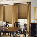 honeycomb window shades with gold-accent curtains classic black wood dining chairs with large wood top table big nature photography with gold-tone frame  classic cabinetry system in black