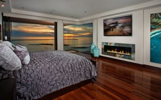 interesting bedroom idea with wonderful fireplace also gorogeus beach view outside and futuristic silver bedsheet in laminate flooring