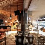 interesting cafe design with wavy ceiling concpet feat wonderful classic wooden seating and ravishing black bar in concrete flooring