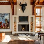interesting rustic room with elegant brown wooden ceiling and alluring beam fireplace with indian painting with furry rug in hardwooden flooring