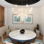 interesting small dining room with round marble table with elegant white chairs also beautiful painting with dramatic chandelier and clustered wall in laminate flooring