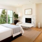 interesting white bedroom with cool wallmount fireplace also astonishing large glass window with ravishing green plant in laminate flooring idea