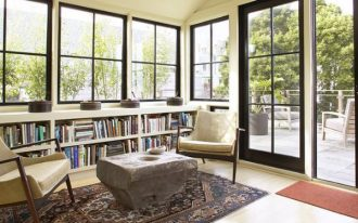 large under window book shelves  sliding glass door with black wood frames  red entryway rug  shabby-look-wood table a pair of reading chairs in cream color Persian rug