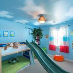 Light Blue Painted Wall Wooden Bed Small Sliding Toy Gray Carpet Animal Wall Sticker Light Blue Ceiling With Cloud Wooden Book Shelves Simple Pendant Lamp