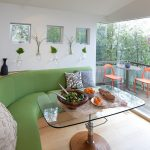 long curved banquette seat in green  accent pillows two bright orange chairs sqaure transparent glass table a set of dishes artistic wood abstract statue attractive hanging glass floral pots mini porch with a set of porch furniture