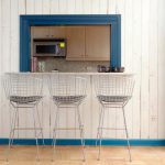 metal stools with grey seat white wood outdoor wall with turquoise trim wood-like tiled flooring dark blue framed kitchen pass through wood upper cabinets grey granite counter