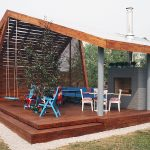 modern outdoor pavilion construction with timber wall system a pair of blue chairs  a blue bench with back feature patio furniture with red-patterns seating  hardwood floor for pavilion