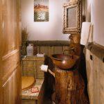 nature themed bathroom wood door white wall wood half wall wood toilet wood-like toilet seat wood-like vanity glass vase black sconce white towel brown round sink