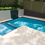 ooutdoor plunge pool with divider elegant cream marble flooring green garden